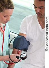 nurse measuring the blood pressure of a patient