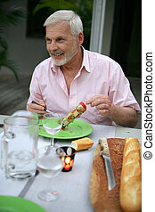 senior man on vacation eating in a restaurant