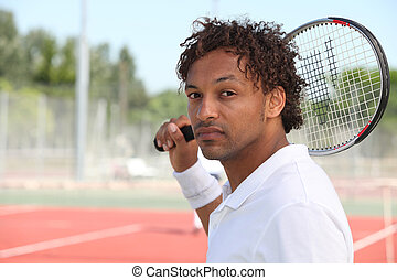 Male tennis player holding racquet over shoulder during game...
