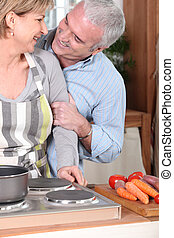 Smiling mature couple cooking