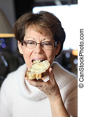 Woman eating a slice of buttered bread