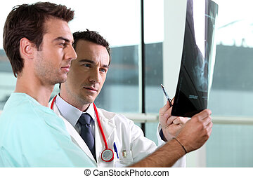 Two medical colleagues looking at x-ray image