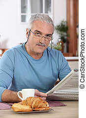 Middle-aged man reading newspaper whilst eating breakfast