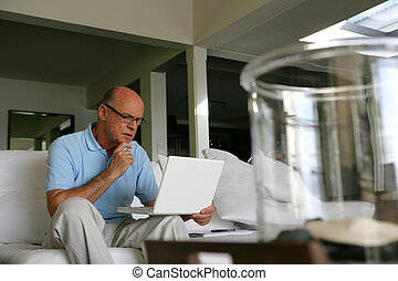 Bald man using his laptop at home