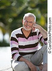 Elderly man sat in garden