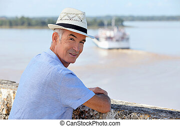 Man in a straw hat watching a ferry cross the Gironde...
