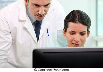 Nurse and doctor looking at computer screen