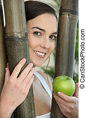 portrait of smiling brunette behind bamboos with green apple