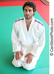 Adult male kneeling on mat in martial arts clothing