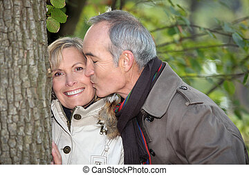 Older man kissing his partner under a tree