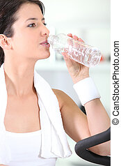 Woman drinking from water bottle in gym