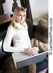 Woman sat in sofa with coffee and laptop