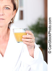 Mature woman drinking juice