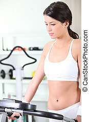 Healthy woman using cross trainer