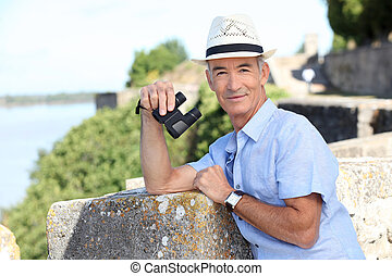 Older male tourist with binoculars leaning on the citadel...
