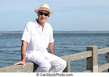 Senior in a straw panama hat sitting by the water