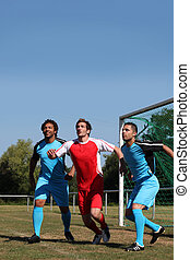 Three footballers waiting for the ball in front of goal