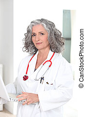 female doctor holding a laptop