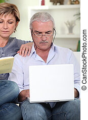 Middle-aged couple sat on sofa with laptop and book