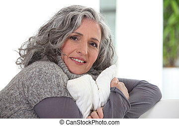 Grey-haired lady holding cushion