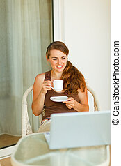 Young woman having coffee and looking in laptop on terrace