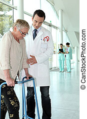 Doctor helping a patient with a walking frame