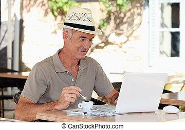 Grey haired man drinking coffee on terrace with laptop...