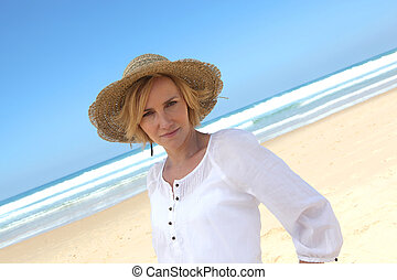 Angled shot of woman in a straw hat on a beautiful sandy...