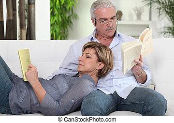 Couple reading on their sofa