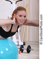 young woman doing stability ball abs exercises