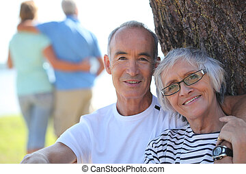 Relaxed older couple sitting in the shade of a tree on a...