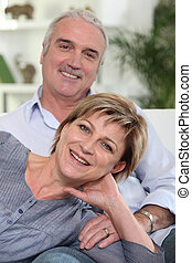 Middle-aged couple sat together on sofa