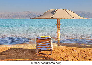 The beach umbrella and a chaise lounge expect tourists -...