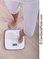 Cropped shot of a woman stepping a pair of scales