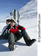 Two skiers sat taking a break