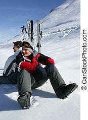 Two skiers sat taking a break