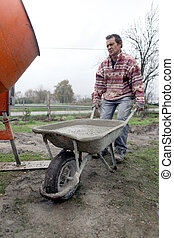 Man transporting cement in wheelbarrow