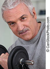 senior man doing exercises with a dumbbell