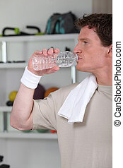 Young man, drinking water after a workout