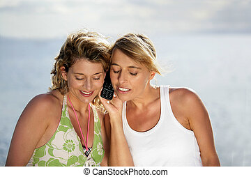 Women on holiday looking at their mobile phone