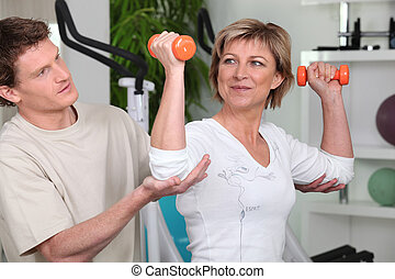 Mature woman working out with a personal trainer