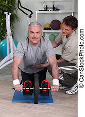 Middle-aged man working with personal trainer