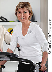 Mature woman using an exercise machine