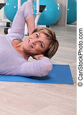 Woman exercising on a gym mat