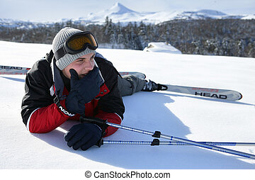 male skier laying down in snow