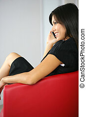 Businesswoman making call whilst sat in designer leather chair