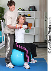 Mature woman working out with coach