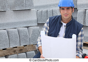 Construction worker standing next to pallets of concrete...