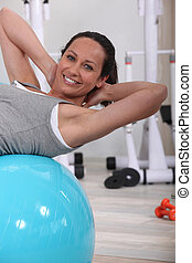 woman doing sit-ups on gym ball