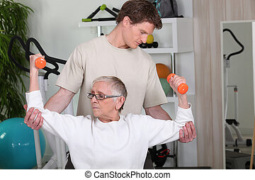 Senior woman working out with a personal trainer